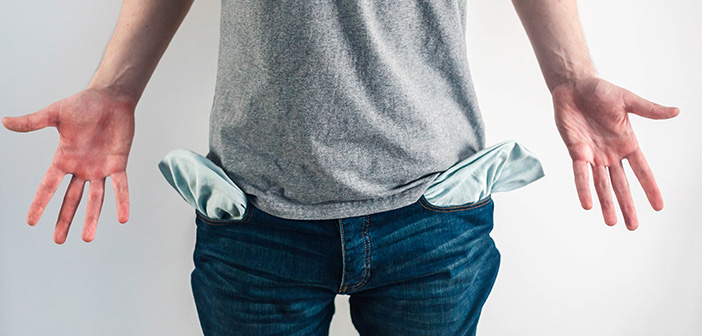 male showing empty pockets implying moneyless