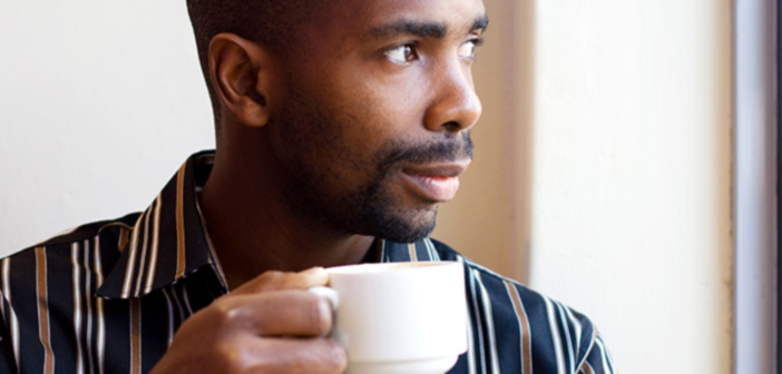 african american man drinking coffee looking out a window
